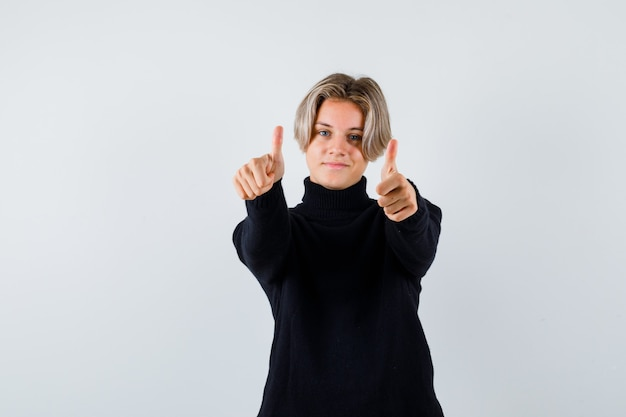 Teen boy in black sweater showing ok gesture and looking pleased , front view.