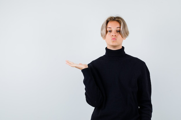 Teen boy in black sweater spreading palm and looking curious , front view.