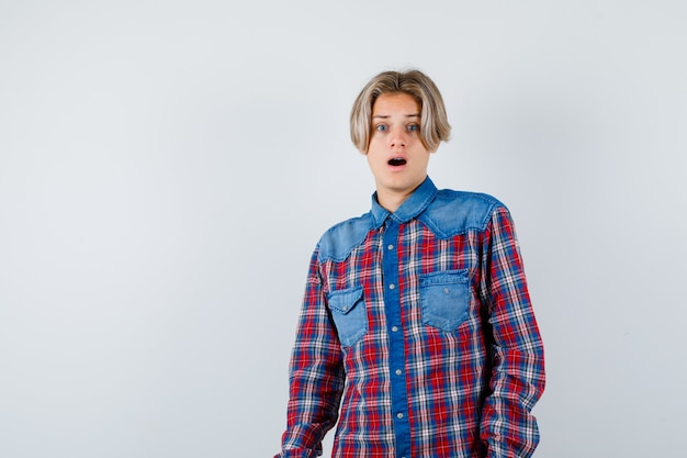 Teen boy in checkered shirt and looking scared , front view.