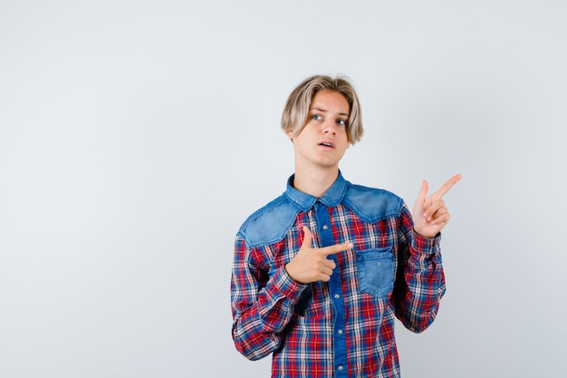 Teen boy in checkered shirt pointing aside and looking thoughtful , front view.