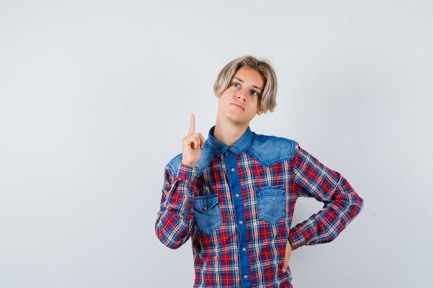 Teen boy in checkered shirt pointing up and looking pensive , front view.