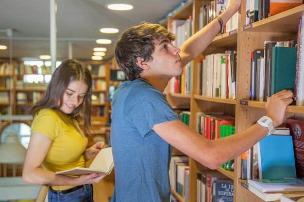 Teen boy choosing book near reading girlfriend