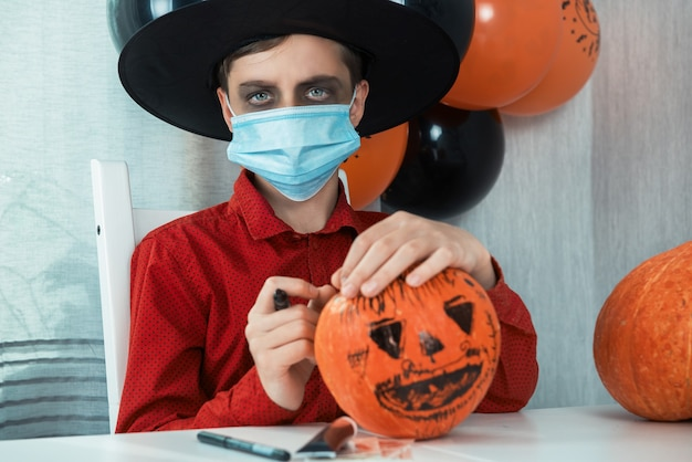 Teen boy in costume and face masks to protect against covid-19 drawing a pumpkin for the halloween celebration