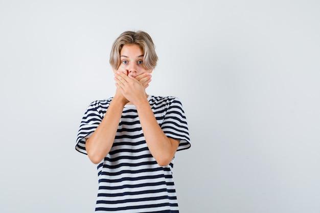 Мальчик-подросток закрывает рот руками в футболке и выглядит испуганным. передний план.
