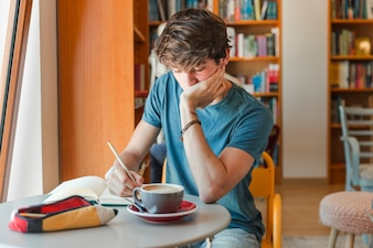Teen boy doing homework in library