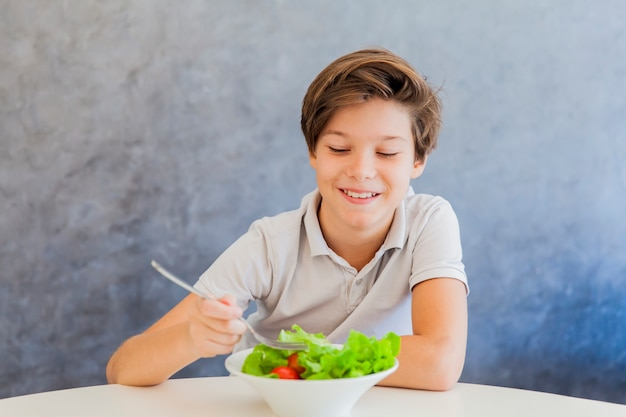 Teen boy eating salad