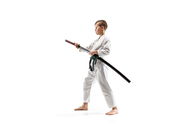 Teen boy fighting at aikido training in martial arts school. healthy lifestyle and sports concept. fightrer in white kimono on white wall. karate man with concentrated face in uniform.