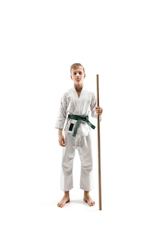 Teen boy fighting with wooden sword at aikido training in martial arts school