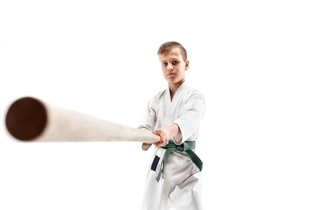 武道学校の合気道の訓練で木刀と戦う 10 代の少年。健康的なライフスタイルとスポーツのコンセプト。白い背景に白い着物を着た格闘家。制服を着た空手の男。