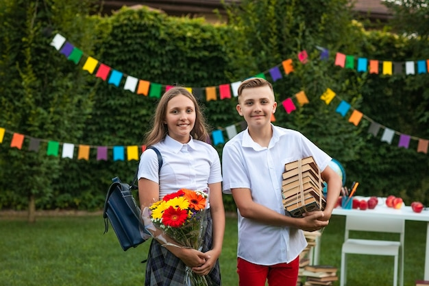 Teen boy and girl in school uniform holding bouquet of flowers and pile of books