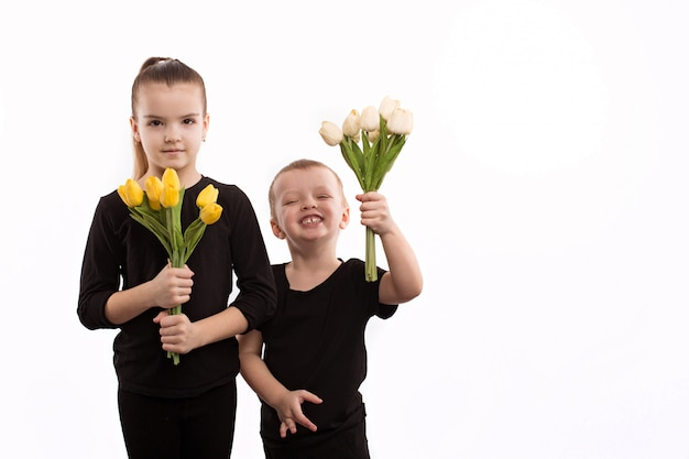 Teen boy and girl with bouquet of tulips. portrait of happy brother and sister on white background.