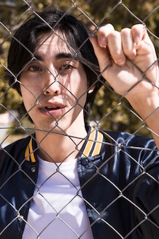 Teen boy gripping fence in street