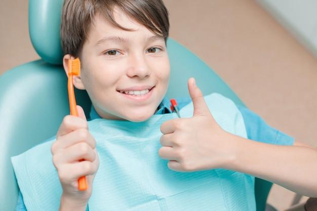 Teen boy having dental treatment at dentists office healthy teeth dental care concept