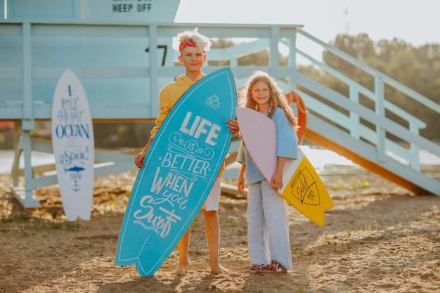 青いサーフボードを持っている十代の少年とライフガードタワーのそばに白と黄色のサーフボードを持っている女の子