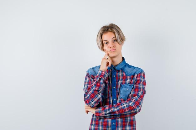 체크 무늬 셔츠에 뺨에 손가락을 잡고 잠겨있는 찾고 십 대 소년, 전면보기.