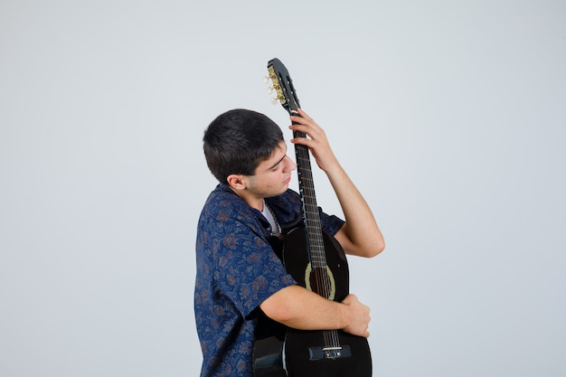 Teen boy holding guitar on chest in t-shirt and looking confident