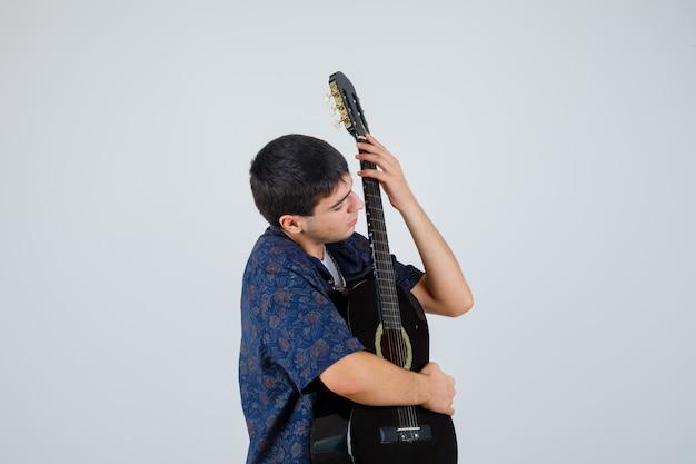 Tシャツを着て胸にギターを持って自信を持って見える10代の少年