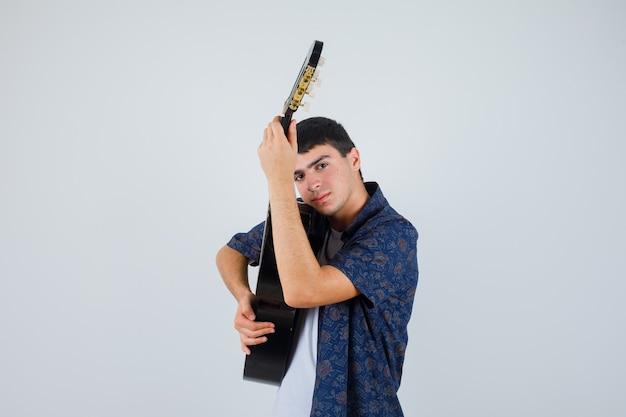 Мальчик-подросток держит гитару на груди в футболке и выглядит уверенно