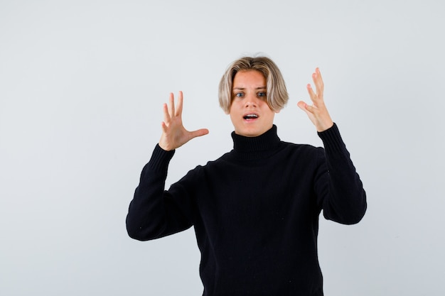 Teen boy holding palms near face in black sweater and looking dissatisfied , front view.