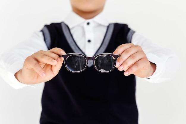 Мальчик-подросток держит в руках очки перед собой. дети, офтальмология и концепция здравоохранения