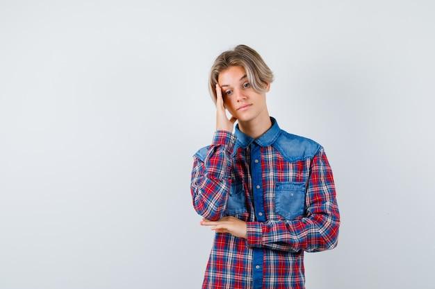 手に頭を傾けて物思いにふける、正面図の市松模様のシャツを着た10代の少年。