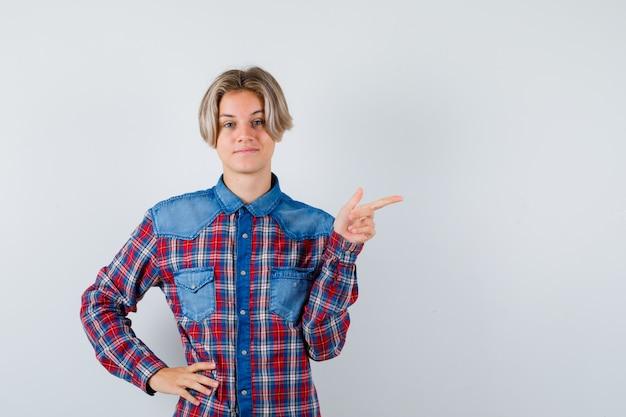 右側を指して、満足そうに見える市松模様のシャツを着た10代の少年、正面図。