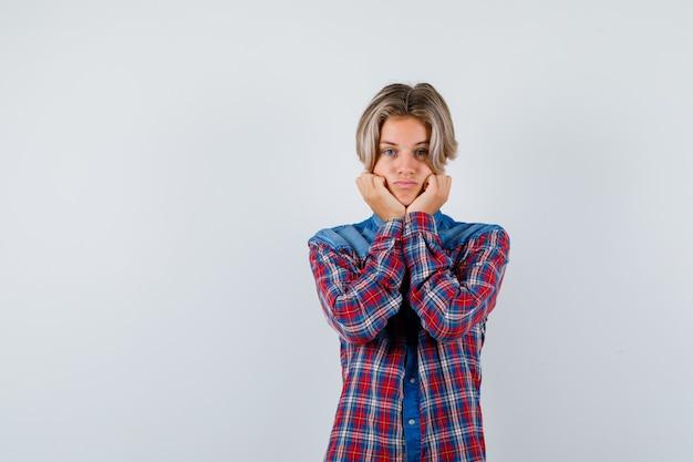 手にあごを支え、注意深く見ている市松模様のシャツを着た10代の少年、正面図。