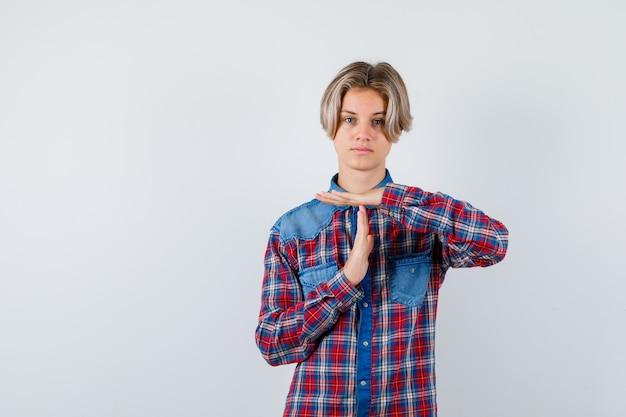 체크 무늬 셔츠를 입은 10대 소년은 시간 휴식 제스처를 보여주고 자신감 있고 앞모습을 보고 있습니다.