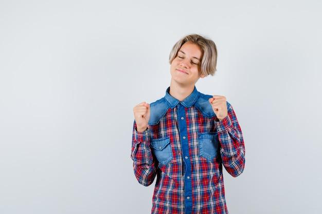 Мальчик-подросток в клетчатой рубашке показывает жест победителя и выглядит удачливым, вид спереди.