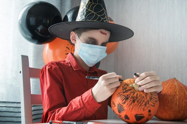 ハロウィーンのお祝いのためにカボチャを描くcovid-19から保護するための衣装とフェイスマスクの10代の少年