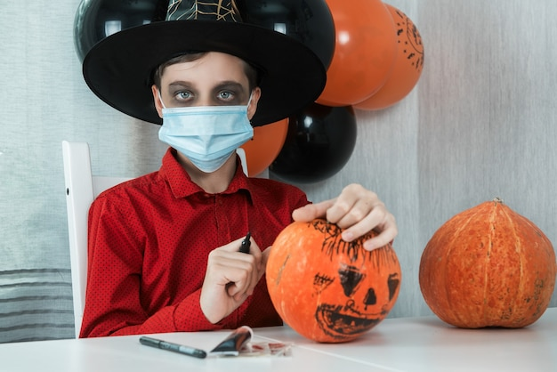 Мальчик-подросток в костюме готовится к празднованию хэллоуина, рисуя тыкву. карнавал на хэллоуин в новой реальности с концепцией пандемии