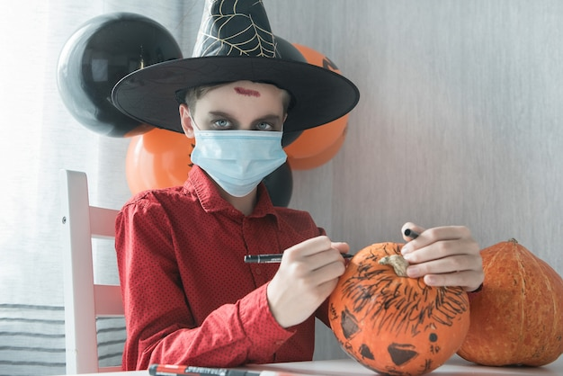 カボチャを描くハロウィーンのお祝いの準備をしている衣装を着た10代の少年。パンデミックの概念を持つ新しい現実とハロウィーンのカーニバル