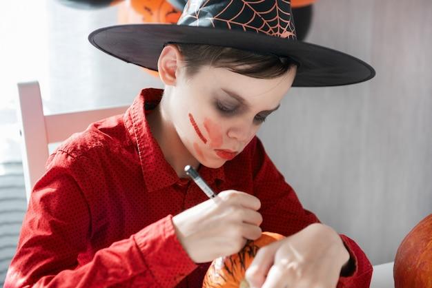 カボチャを描くハロウィーンのお祝いの準備をしている衣装を着た10代の少年
