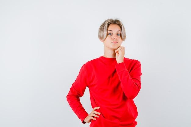 あごに指を保ち、思慮深く、正面図を探している赤いセーターの10代の少年。