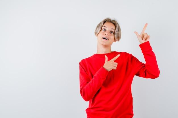 Мальчик-подросток в красном свитере указывая вверх, открывая рот и выглядя изумленным, вид спереди.