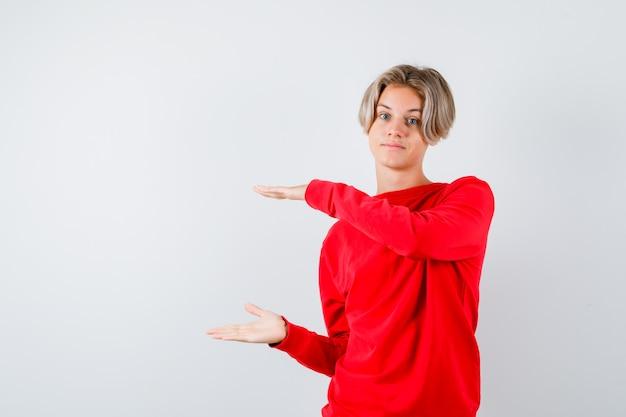 Подросток мальчик в красном свитере показывает знак размера и выглядит уверенно, вид спереди.