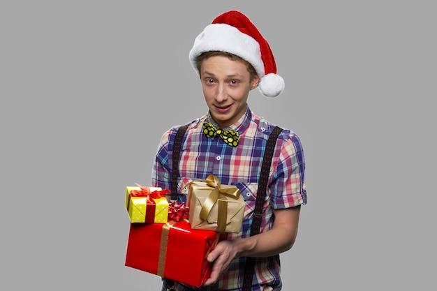 Подросток мальчик в шляпе санта-клауса, держа подарочные коробки. портрет подростка, держащего рождественские подарки на сером фоне.