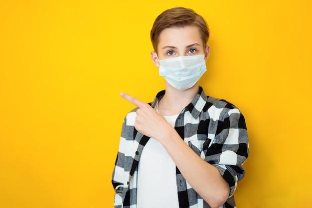黄色の背景で隔離のポーズの滅菌フェイスマスクの十代の少年