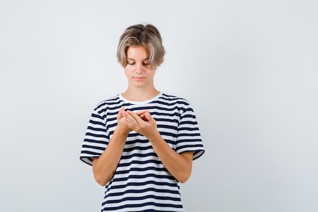 티셔츠를 입은 10대 소년이 손바닥을 바라보고 조심스럽게 정면을 바라보고 있습니다.