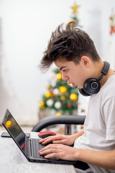 십 대 소년 집에서 헤드폰으로 노트북을 사용합니다. 벽에 크리스마스 트리입니다. 놀란 얼굴