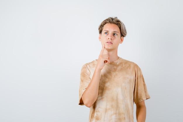 10대 소년이 티셔츠를 입은 턱에 손가락을 대고 정신이 팔려 앞을 바라보고 있습니다.