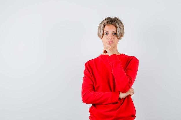 赤いセーターのあごに手を保ち、物思いにふける、正面図を探している十代の少年。