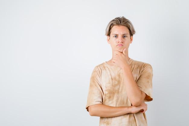 Tシャツのあごに手を置いて思慮深く見える10代の少年。正面図。