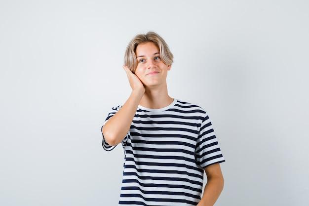 10대 소년은 티셔츠를 입고 머리에 손을 얹고 쾌활하고 앞모습을 보고 있습니다.