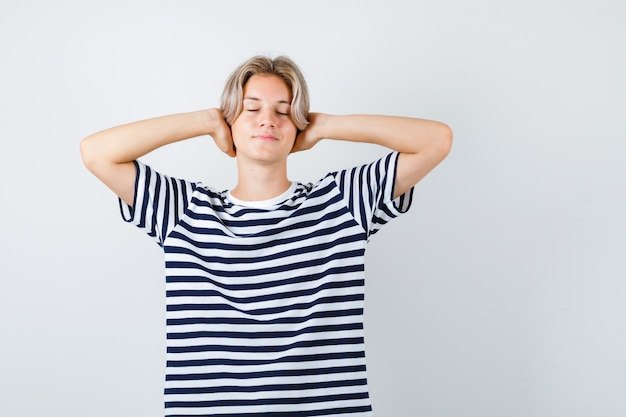 Teen boy keeping hands behind head, closing eyes in t-shirt and looking relaxed. front view.