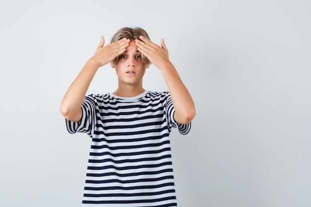Tシャツで額に手を置いて心配そうに見える10代の少年、正面図。