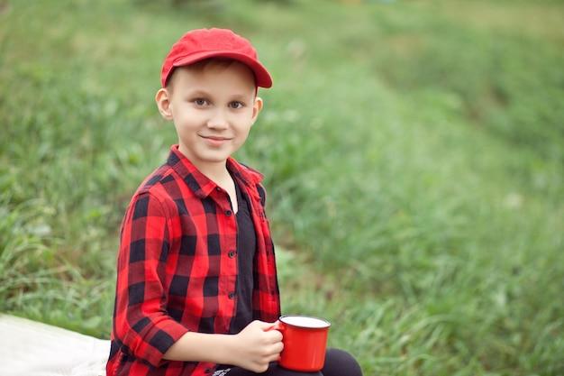Подросток мальчик ребенок в клетчатой рубашке, держа чашку напитка. путешествие, поход, отпуск, концепция кемпинга.