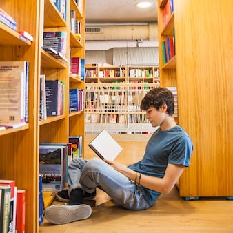 Teen boy leaning on bookcase and reading