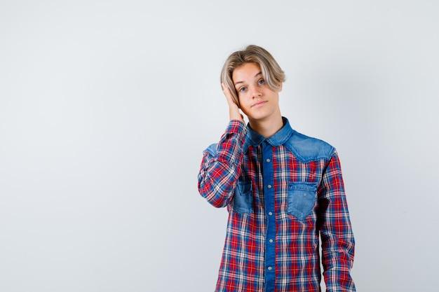 市松模様のシャツを着て頭を抱えて平和に見える10代の少年。正面図。