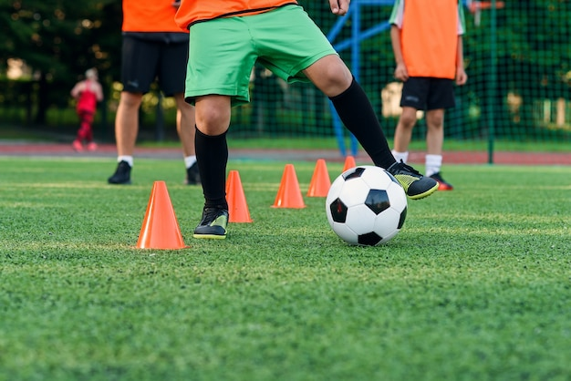 Teen boy learns to circle the ball between training cones at soccer stadium.